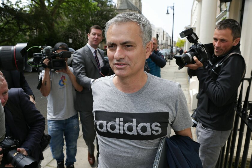 Media reporters surround footbal manager Jose Mourinho as he leaves his house in central London, Friday, May 27, 2016. Manchester United hired Jose Mourinho as its third manager in three years on Friday, entrusting the highly successful Portuguese coach with the job of restoring the status of Engla