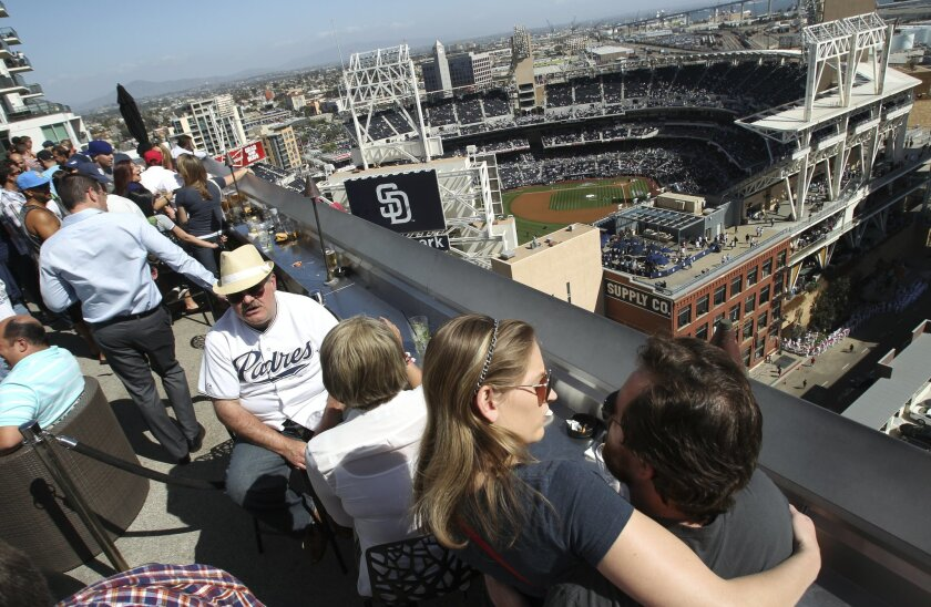 John Donahoe and girlfriend Kimberly Huston hug while they wait for the start of the Padres home opener against the Dodgers while at the Marriott Altitude Sky Lounge.