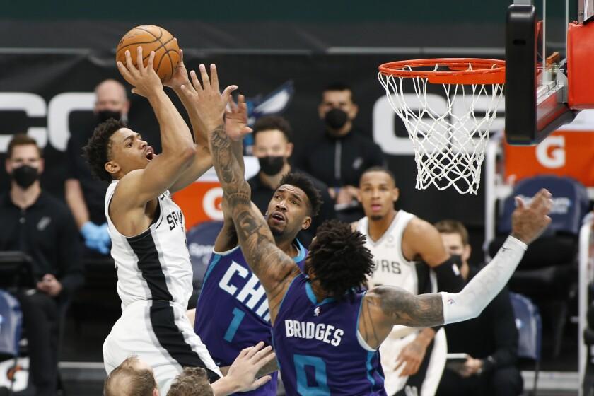 San Antonio Spurs forward Keldon Johnson, left, shoots over Charlotte Hornets guard Malik Monk (1) and forward Miles Bridges during the second half of an NBA basketball game in Charlotte, N.C., Sunday, Feb. 14, 2021. (AP Photo/Nell Redmond)
