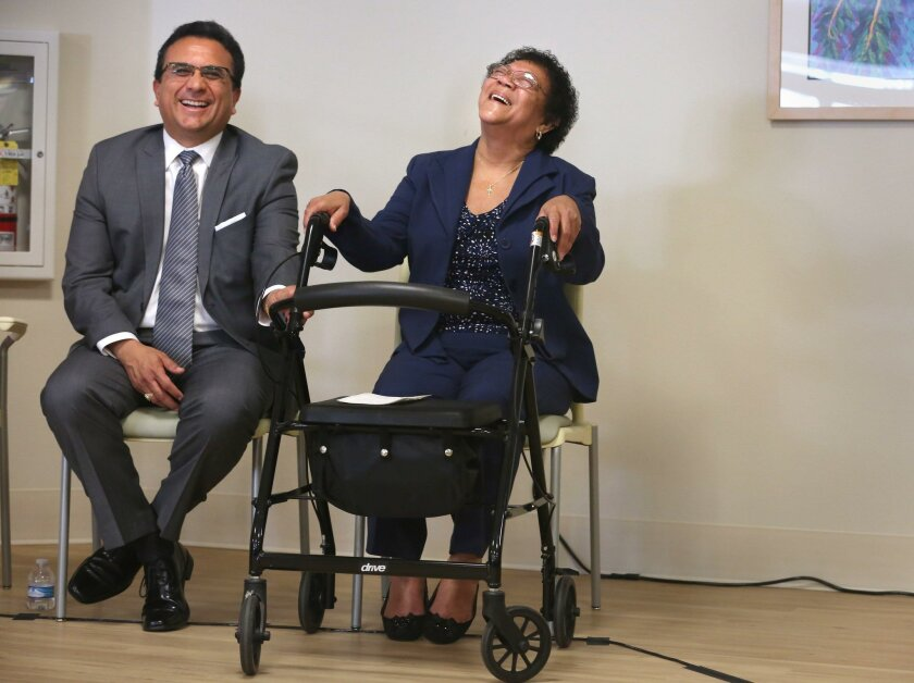 Edward Lopez of the San Diego chapter of Local Initiatives Support Corporation laughs with San Diego Square resident Isara Garrett.