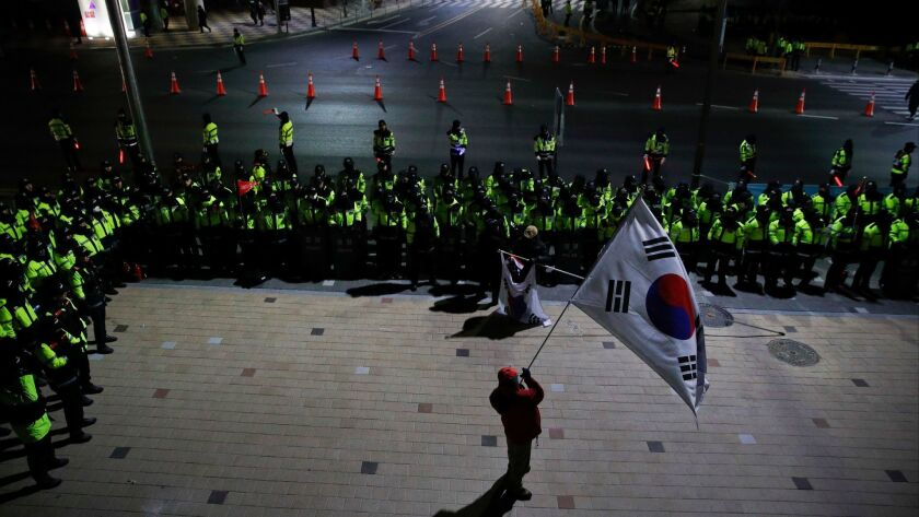 A protester holds a large South Korean flag as he is surrounded by police officers during a rally ou