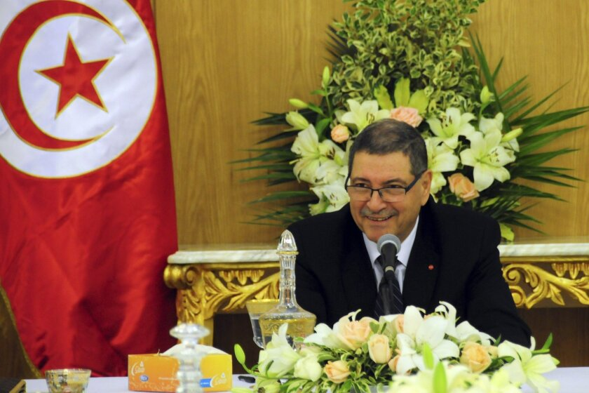 Tunisia's Prime Minister Habib Essid shares a smile with ministers prior to preside over an extraordinary Cabinet meeting in Carthage, outside Tunis, Saturday Jan. 23, 2016. Tunisia's prime minister, Habib Essid, cut short a visit to France as Tunisia's president vowed Friday to end the cycle of unrest that has pummeled towns across the country as authorities imposed a nationwide curfew, five years after the nation, convulsed by protests, overthrew its longtime ruler and moved onto the road to democracy. (AP Photo/Riadh Dridi)