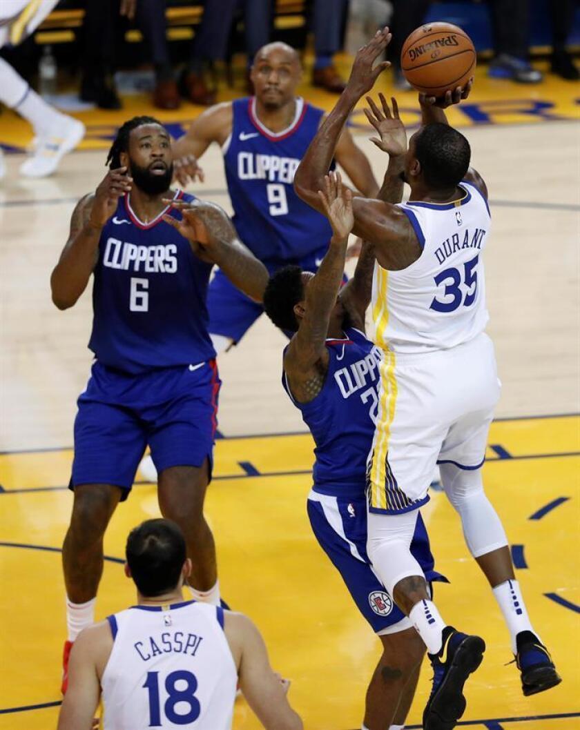 El alero de Golden State Warriors Kevin Durant (d) lanza ante Lou Williams (c) de los LA Clippers, durante su partido de la NBA en el Oracle Arena en Oakland, California, EE. UU., el 10 de enero de 2018. EFE
