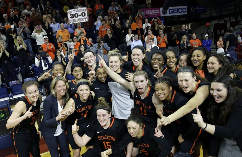 FILE - In this Tuesday, March 10, 2015 file photo, a fan holds a sign as the Princeton players pose for photographs after defeating Pennsylvania in an NCAA college basketball game Tuesday, March 10, 2015, in Philadelphia, Pa. Princeton won 55-42 to end a perfect season. Not everyone is all that ena