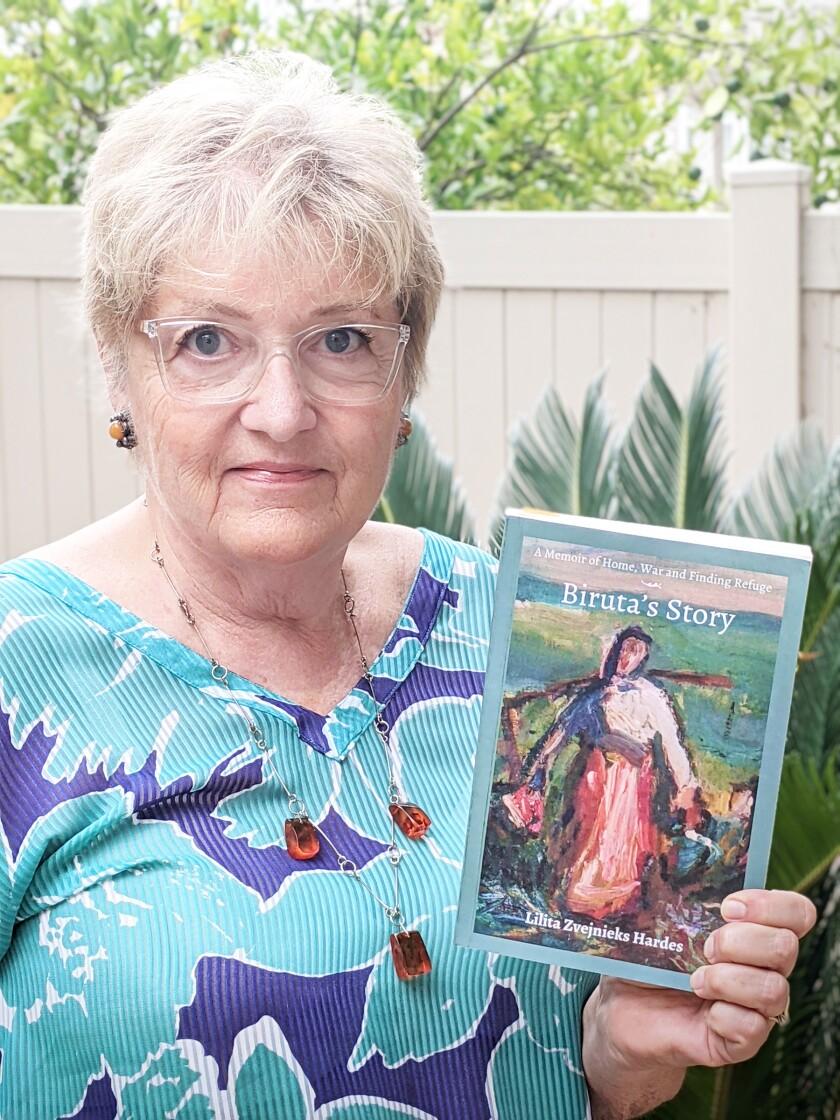 "Lilita Zvejnieks Hardes holding her book, ""A Memoir of Home, War and Finding Refuge — Biruta's Story."""