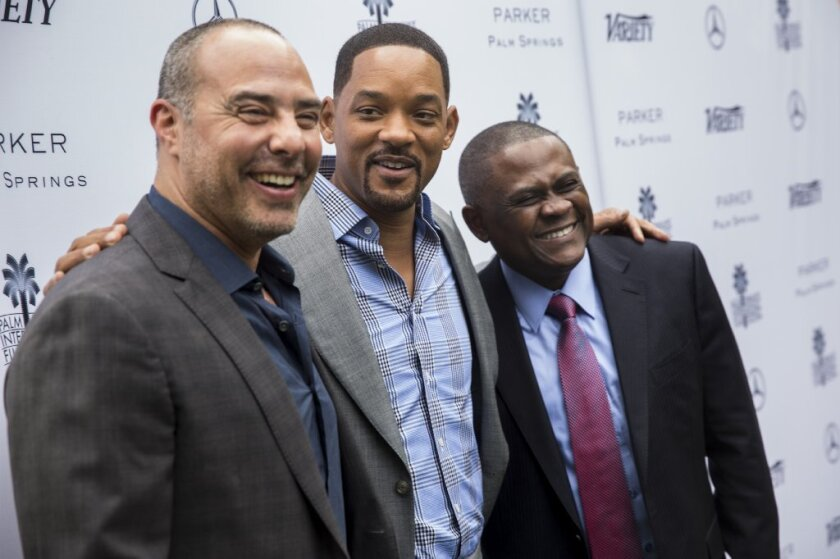 Dr. Bennet Omalu, right, the neuropathologist who found chronic traumatic encephalopathy in an American football player for the first time, with Peter Landesman, left, director of the movie 'Concussion,' and Will Smith.