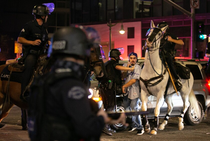 LAPD officers on horseback move in to disperse the crowds in downtown Los Angeles after the Dodgers win the World Series.