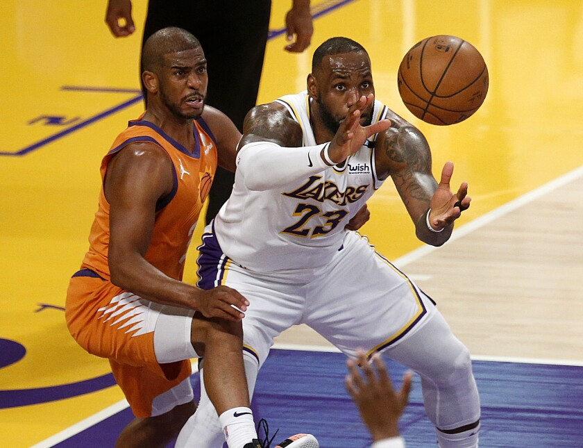 Lakers forward LeBron James receives a pass while under pressure from Phoenix Suns guard Chris Paul.