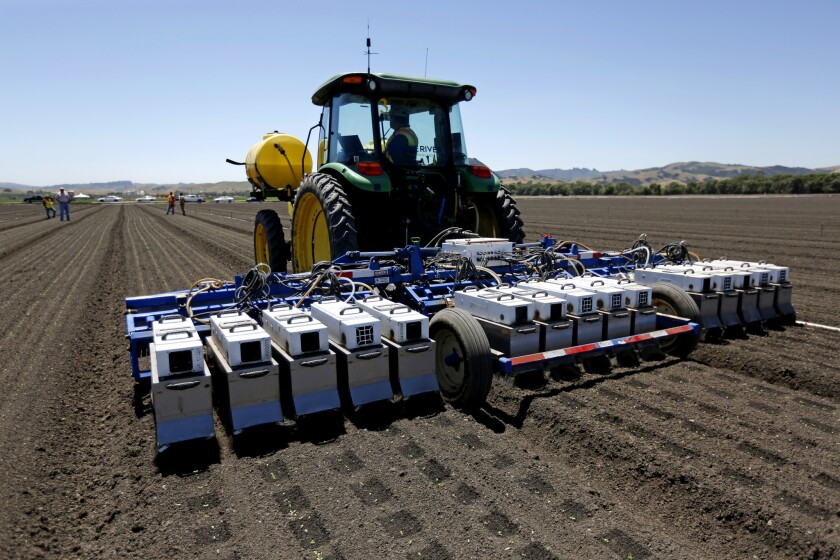 A See and Spray machine manufactured by Blue River Technology uses cameras, computers and precision sprayers to thin a lettuce field in Gilroy, Calif., in May.