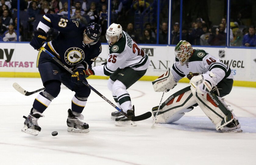 St. Louis Blues' Dmitrij Jaskin (23), of Russia, tries to control the puck as Minnesota Wild's Jonas Brodin (25), of Sweden, and goalie Devan Dubnyk defend during the second period of an NHL hockey game Saturday, Oct. 31, 2015, in St. Louis. (AP Photo/Jeff Roberson)