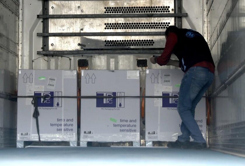 Un trabajador de salud revisa unas cajas de la vacuna contra el coronavirus de AstraZeneca dentro de un camión, en Bab al-Hawa, en el noroeste de Siria, el miércoles 21 de abril de 2021. (AP Foto/Ghaith Alsayed)