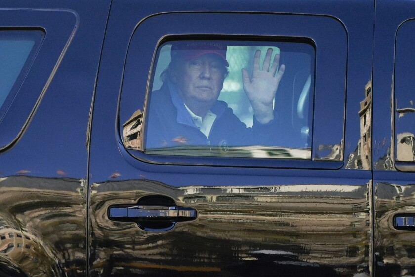 President Trump waves to supporters from his motorcade as people gather for a march Saturday in Washington, D.C.