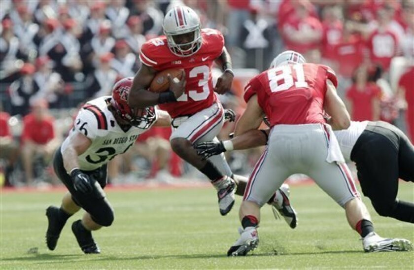 Ohio State quarterback Kenny Guiton, center, runs between tight end Nick Vannett, right, and San Diego State linebacker Nick Tenhaeff during the first quarter of an NCAA college football game Saturday, Sept. 7, 2013, in Columbus, Ohio. (AP Photo/Jay LaPrete)