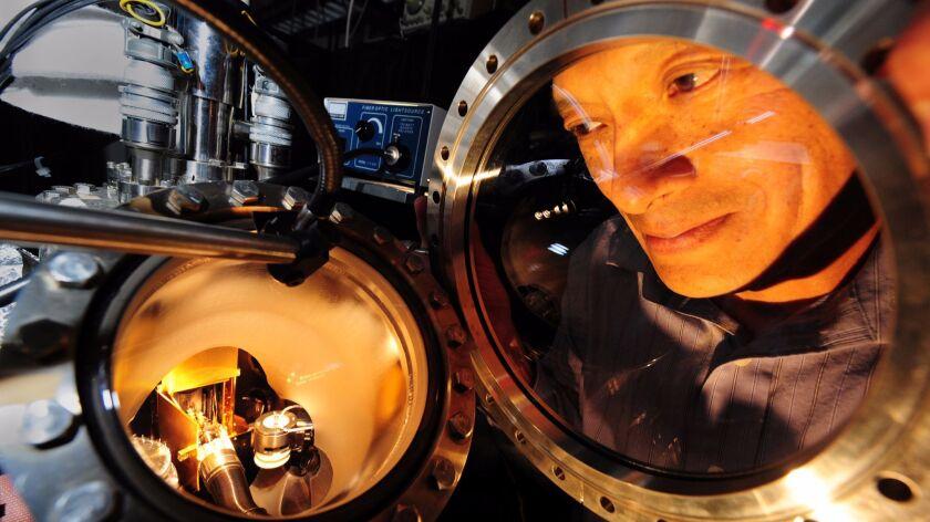 Physics & chemistry professor Wilson Ho peers through one of his powerful homemade microscopes, capa