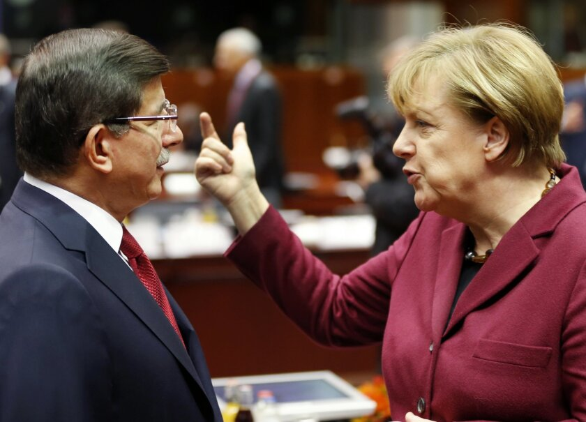 German Chancellor Angela Merkel talks to Turkish Prime Minister Ahmet Davutoglu during an EU-Turkey summit at the EU Council building in Brussels on Sunday, Nov. 29, 2015. At a high-profile summit in Brussels on Sunday, European Union leaders will look to offer Turkey 3 billion euros ($3.2 billion), an easing of visa restrictions and the fast-tracking of its EU membership process in return for tightening border security and take back some migrants who don't qualify for asylum.(AP Photo/Michael Probst)