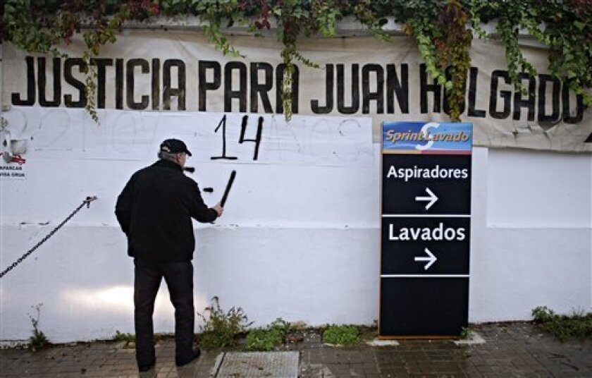 "In this Tuesday, Nov. 30, 2010 picture, Francisco Holgado, better known as ""Father Courage,"" paints the number ""15"" for the fifteen anniversary of the killing of his son Juan Holgado at the gas station where he was murdered in Jerez de la Frontera, southern Spain. Sign at top reads ""Justice for Jua"