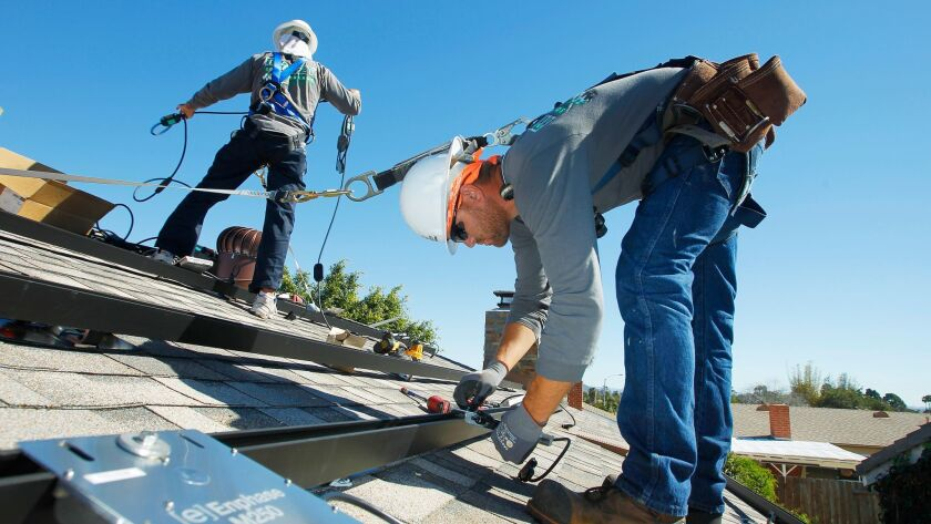 Workers install solar panels on the roof of a house in Serra Mesa.