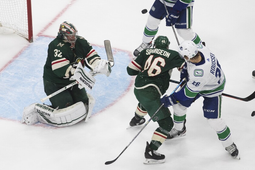 Minnesota Wild goalie Alex Stalock (32) makes the save as Jared Spurgeon (46) and Vancouver Canucks' Antoine Roussel (26) battle in front during the second period of an NHL hockey qualifying round game, Friday, Aug. 7, 2020, in Edmonton, Alberta. (Jason Franson/The Canadian Press via AP)