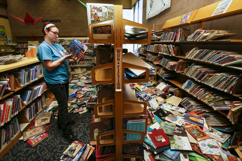 Shalyn Pineda, regional supervisor of Kern County's libraries, picks up books at Ridgecrest Library after Thursday's 6.4 earthquake dislodged bookshelves.