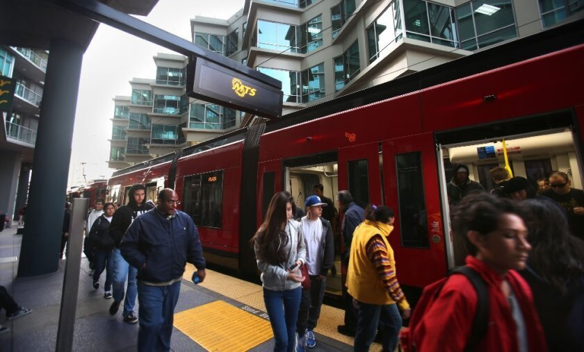 Students headed for San Diego High School or San Diego City College, as well as other trolley users, disembark by the complex that's next to the Smart Corner condo building on Dec. 10. / photo by Peggy Peattie * U-T