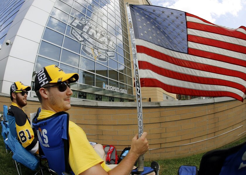 Nick Comito, foreground, and Mitch Bell, left, both of Greensburg, Pa., wave the American Flag on Memorial Day as they wait outside the Consol Energy Center for Game 1 of the Stanley Cup final series between the San Jose Sharks and the Pittsburgh Penguins Monday, May 30, 2016, in Pittsburgh. (AP Ph