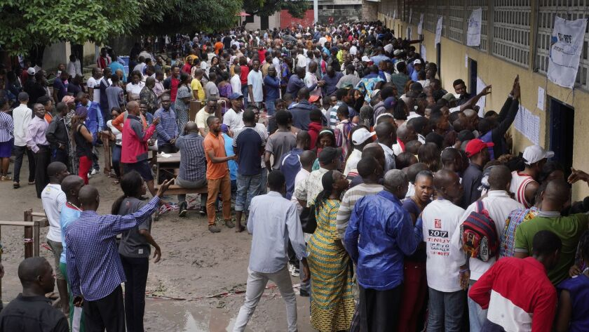 Hundreds of Congolese waiting at a school in Kinshasa's Limete district storm polling stations on Dec. 30, 2018, after voter listings were finally posted five hours after the official start of balloting.