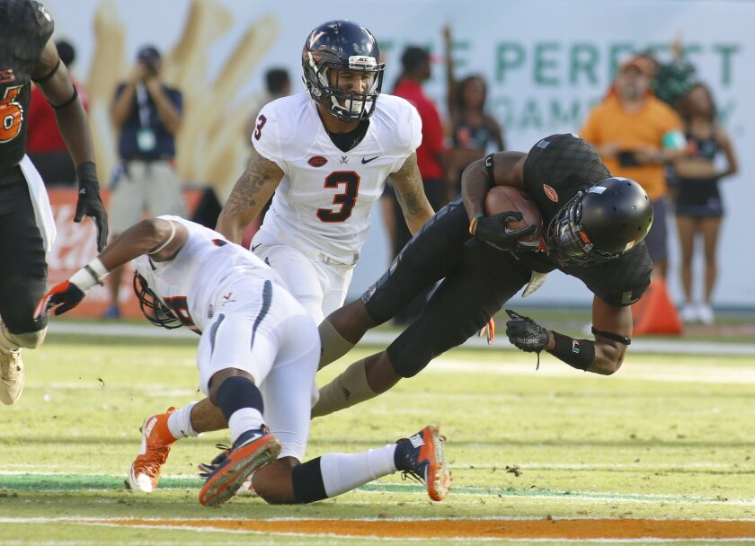 Miami wide receiver Stacy Coley (3) picks up yardage in the second quarter before being brought down by defenders including Virginia safety Quin Blanding (3) in an NCAA college football game, Saturday, Nov. 7, 2015, in Miami Gardens, Fla. (AP Photo/Joe Skipper)