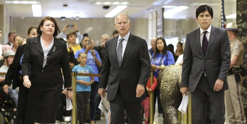 FILE-- In this June 16, 2015 file photo Calif., Gov. Jerry Brown, flanked by Assembly Speaker Toni Atkins, D-San Diego, left, and Senate President Pro Tem Kevin de Leon, D-Los Angeles, right, walk to a news conference to announce a budget agreement they reached. (AP Photo/Rich Pedroncelli,file)