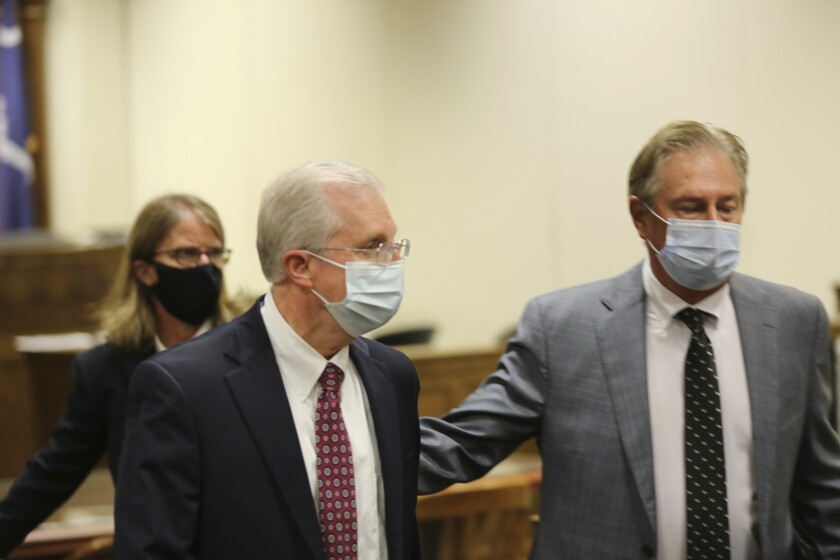 Former SCANA CEO Kevin Marsh, center, is led out of the courtroom by attorney Robert Bolchoz, right, after a South Carolina judge accepted a plea deal that included a two-year federal prison term for Marsh on Monday, Oct. 11, 2021, in Spartanburg, S.C. Marsh is the first executive to go to prison for the failed project to build two nuclear reactors which cost ratepayers billions of dollars and never generated a watt of power. (AP Photo/Jeffrey Collins)