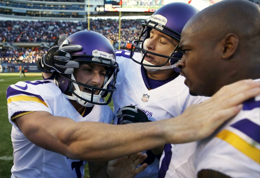 Minnesota Vikings kicker Blair Walsh (3) celebrates his game winning field goal with Jeff Locke, center, and Adrian Peterson (28) during the second half of an NFL football game, Sunday, Nov. 1, 2015, in Chicago. The Vikings won 23-20. (AP Photo/Charles Rex Arbogast)