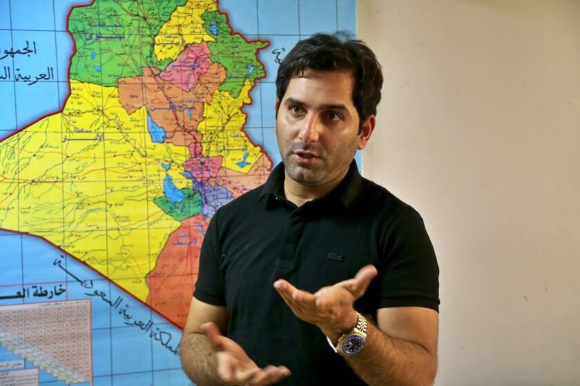 Raslan Haddad, el presentador del programa televisivo de bromas Tannab Raslan, habla frente a un mapa de Irak durante una entrevista con The Associated Press en Bagdad, Irak, el jueves 5 de mayo de 2021. (AP Foto/Hadi Mizban)