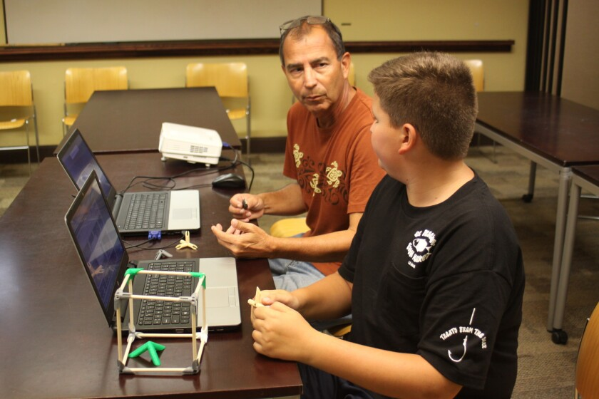 Instructor Marco Balcazar and 13-year-old Ben Davis discuss 3-D printing. The box in the foreground is similar to the shoe rack Marco made at home.