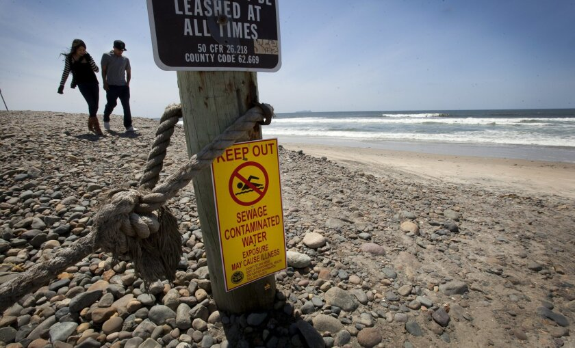 Ana Mendoza, left, and Anthony Villalpando walk past a contaminated-water warning sign at the end of Seacoast Drive in Imperial Beach earlier this month. HOWARD LIPIN • U-T