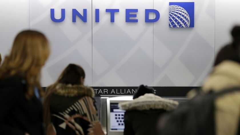 People stand in line at a United Airlines counter at LaGuardia Airport in New York. The airlines' brand has taken a beating after a dog stored in an overhead bin during a flight from Houston to New York died last week.