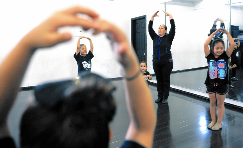 Lourdes Perez, owner of Spotlight Dance Studio in Cudahy, teaches a folkloric dance class. She speaks almost entirely in Spanish, while most of her students, though Latino, speak English.