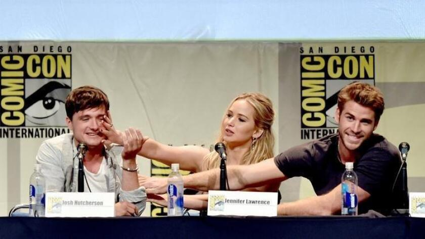 """Actors Josh Hutcherson, Jennifer Lawrence and Liam Hemsworth speak at the """"The Hunger Games: Mockingjay Part 2"""" panel during Comic-Con International 2015 at the San Diego Convention Center. (Kevin Winter / Getty Images)"""