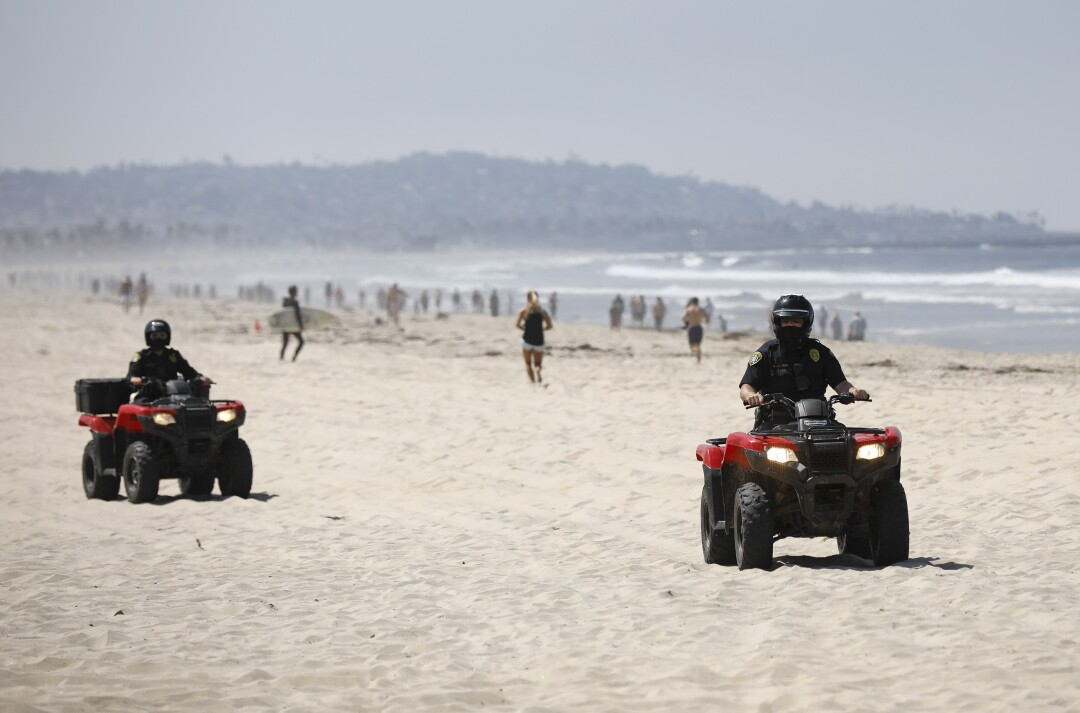 San Diego Police officers patrol Pacific Beach after local beaches reopened to activities such as walking, running, and surfing on April 27, 2020. Beaches have been closed for several weeks due to the coronavirus. The boardwalks and congregating on the sand are still prohibited.