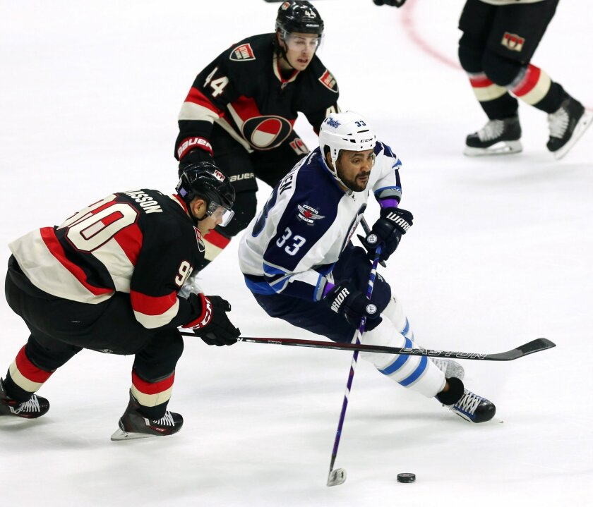 Winnipeg Jets' Dustin Byfuglien (33) fights for control of the puck with Ottawa Senators' Alex Chiasson (90) and Jean-Gabriel Pageau (44) during the first period of an NHL hockey game Thursday, Nov. 5, 2015, in Ottawa, Ontario. (Fred Chartrand/The Canadian Press via AP)