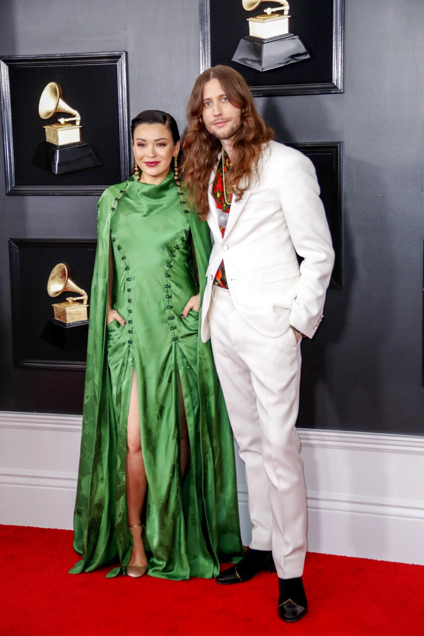 Serena McKinney, in a green dress, and Ludwig Göransson, in a white suit, on the red carpet at the 61st Grammy Awards.