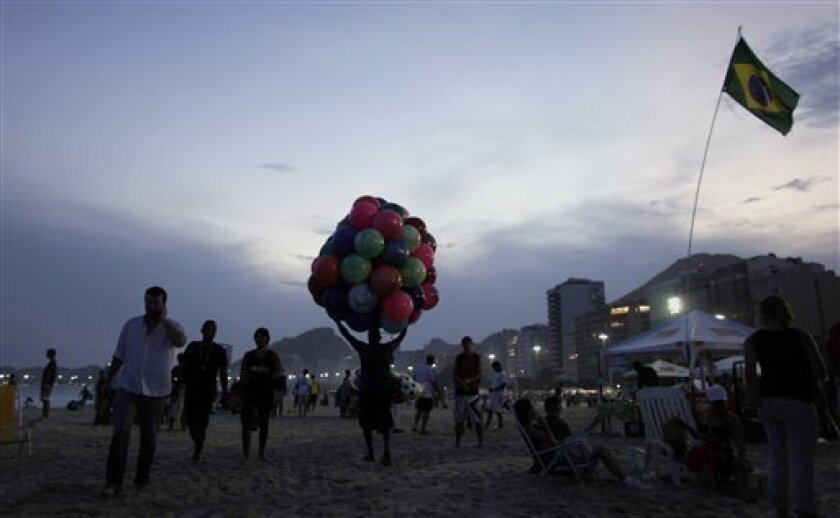 People walk by the beach after celebrating the announcement that Rio de Janeiro will host the 2016 Olympic Games on Copacabana beach in Rio de Janeiro, Friday, Oct. 2, 2009. Nearly 50,000 people cheered in celebration when Rio de Janeiro was announced as host of the 2016 Olympics, jumping and shouting in a Carnival-like party on Copacabana beach. (AP Photo/Natacha Pisarenko)
