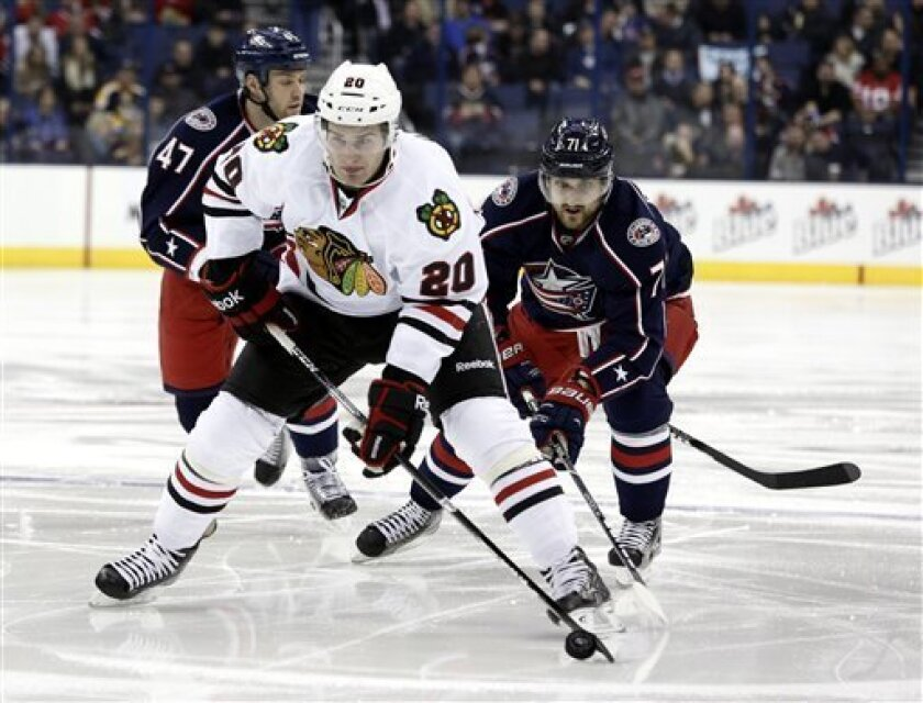 Chicago Blackhawks' Brandon Saad (20) carries the puck against Columbus Blue Jackets' Dalton Prout (47) and Nick Foligno (71) during the first period of an NHL hockey game in Columbus, Ohio, Thursday, March 14, 2013. The Blackhawks won 2-1 in a shootout. (AP Photo/Paul Vernon)