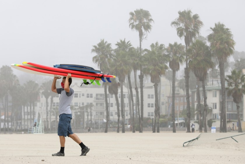 Peter Gratzinger of Pacific Palisades carries boogie boards and surfboards at Santa Monica State Beach.