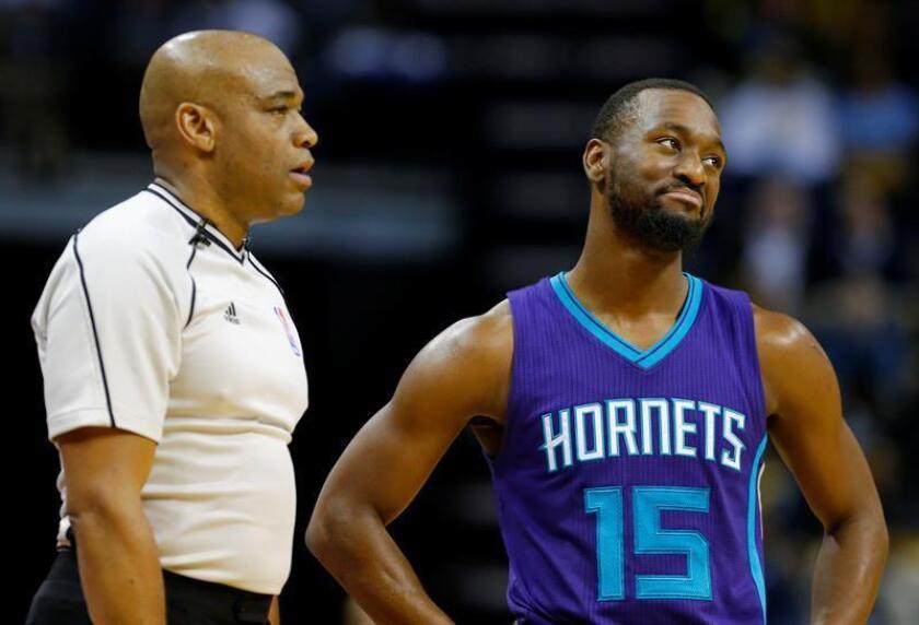 Kemba Walker (d) de Hornets habla con un juez en un juego. EFE/Archivo