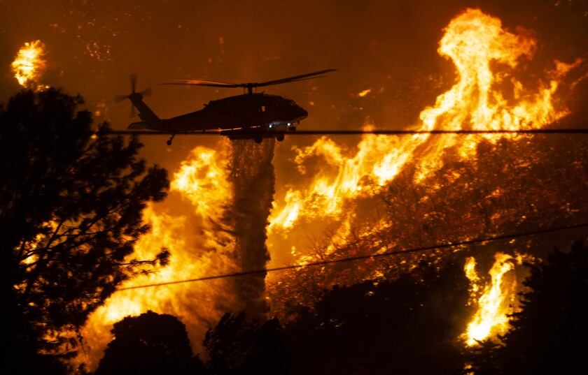 A firefighting helicopter drops water as flames from the Lake fire rage in the Angeles National Forest