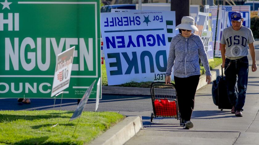 Pedestrians walk past a row of political signs and posters along Bolsa Avenue in Westminster. In Orange County, 24 people of Vietnamese descent are running for public office.