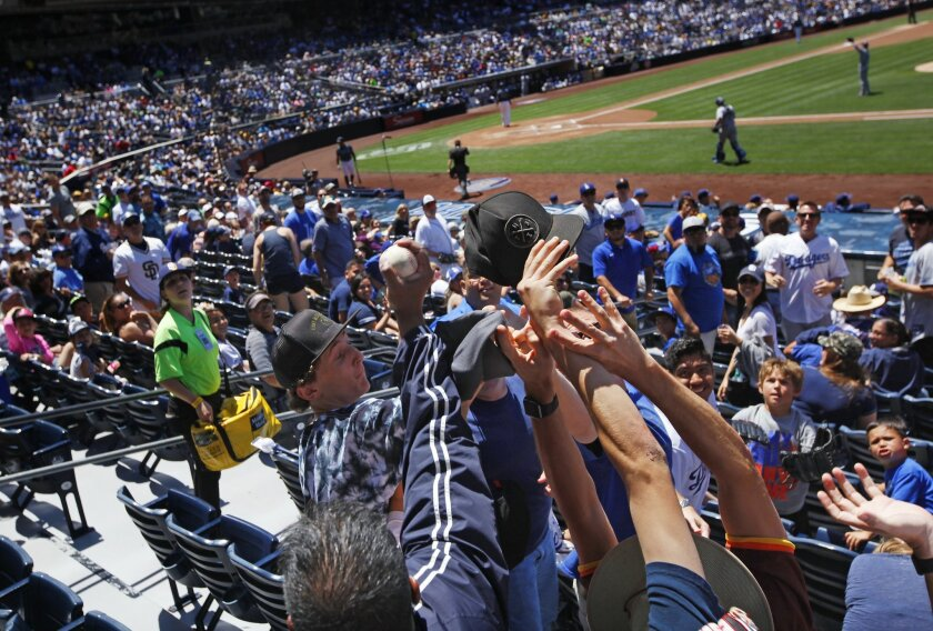 A fan catches a foul ball during the Padres-Dodgers game at Petco Park.