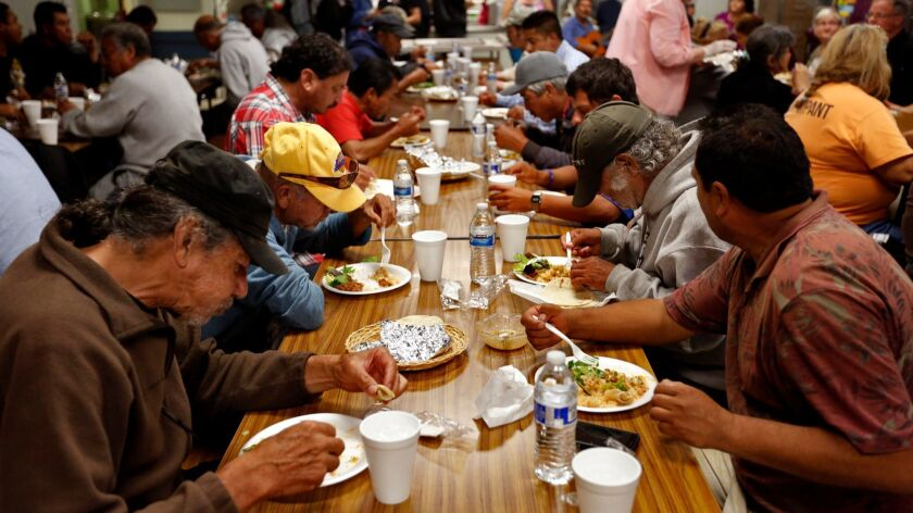 Homeless men, most of them undocumented Latinos, have a meal at a facility that also offers shelter