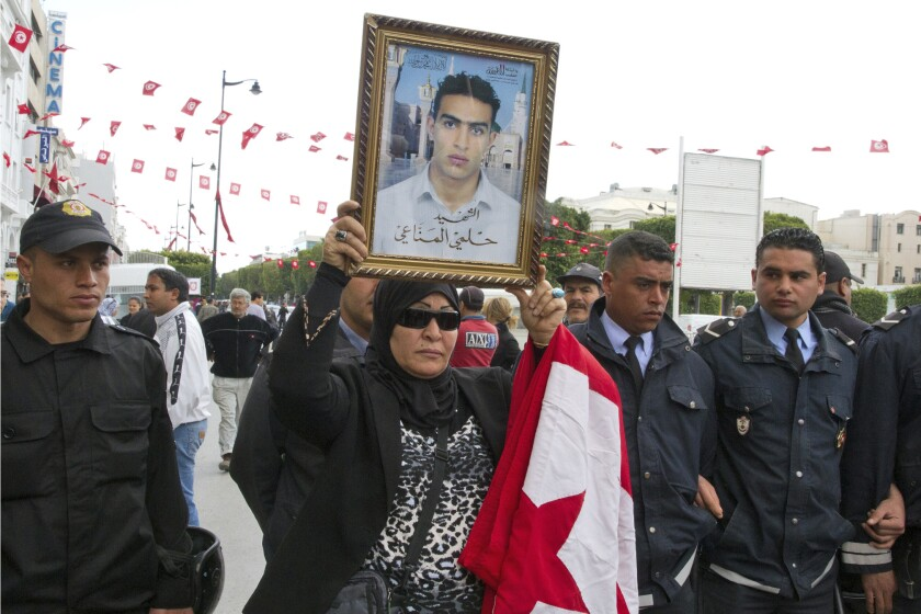 FILE - In this April 9, 2012 file photo, a Tunisian woman holds a poster of her martyr son named Helmi Manaai, written under the photo, during a protest in Tunis. Since winning a parliamentary seat in 2019, Tunisian lawmaker Abir Moussi has become one of the country's most popular, and most controversial, politicians, riding a wave of nostalgia for a more stable and prosperous time, just as Tunisia marks 10 years since protesters overthrew autocratic former President Zine El Abidine Ben Ali. Since 2011, Tunisia has been plagued by sinking wages, growing joblessness and worsening public services. Unemployment has risen amid the coronavirus pandemic from 15% to 18%. Attempts to migrate to Europe by sea have soared. (AP Photo/Amine Landoulsi, File)