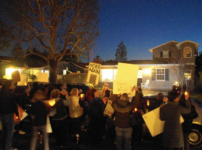 About 50 people gathered in front of the Eastside Costa Mesa home of Rep. Dana Rohrabacher on Thursday night, calling on him to hold a town hall meeting and advocating against repealing the Patient Protection and Affordable Care Act.