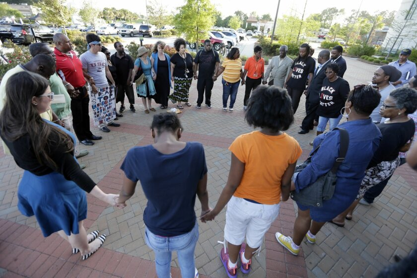 People hold hands in prayer after the killing of Walter Scott by a police officer in North Charleston, S.C., in 2015.